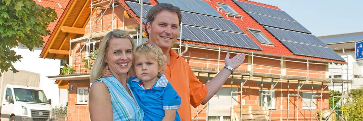 Erneuerbare Energie: Familie vor Neubau mit Photovoltaikanlage