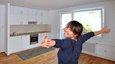 Fördermittel: Frau glücklich in ihrem neuen Zuhause