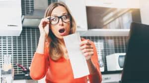 Energiesparen: Frau schaut entsetzt auf ihre Stromrechnung