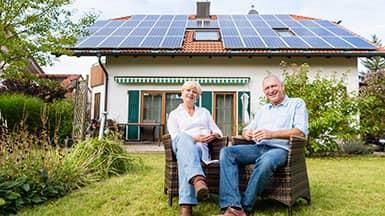 Erneuerbare Energie - Photovoltaik: Paar sitzt im Garten vor Haus mit Photovoltaikanlage