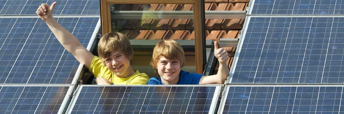 Erneuerbare Energie: Kinder winken aus Dachfenster umgeben von Photovoltaikanlage