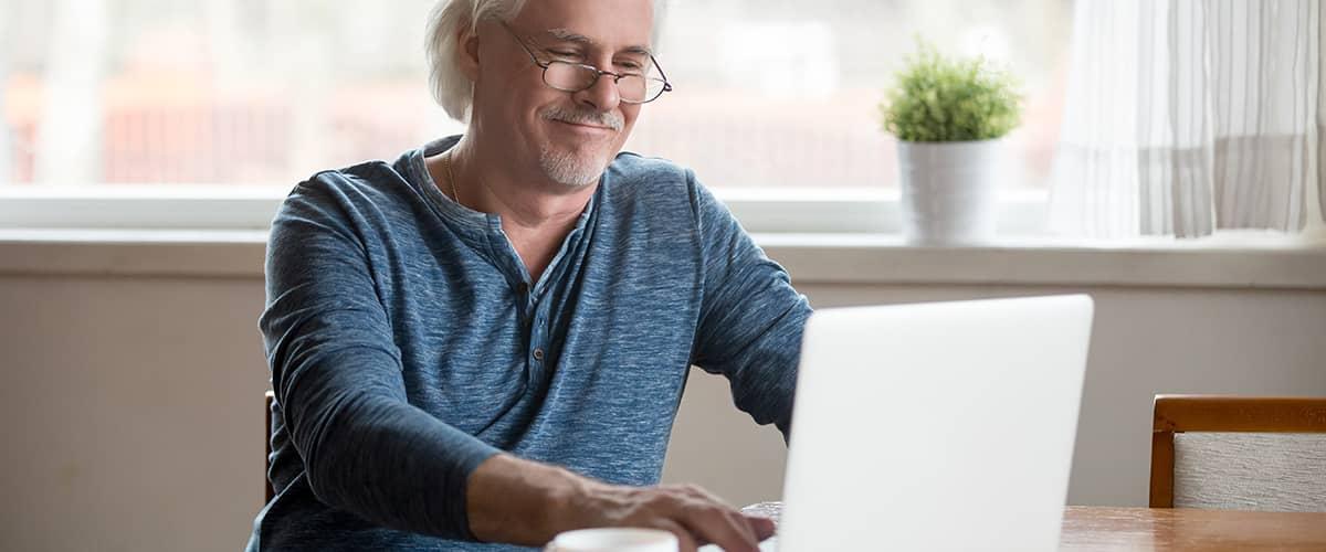 Älterer Mann schaut zufrieden in sein Laptop.
