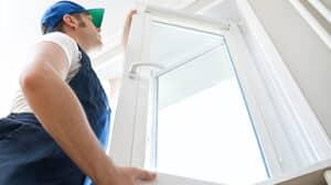 Monteur im blauen Overall setzt einen modernen Fensterflügel ein.