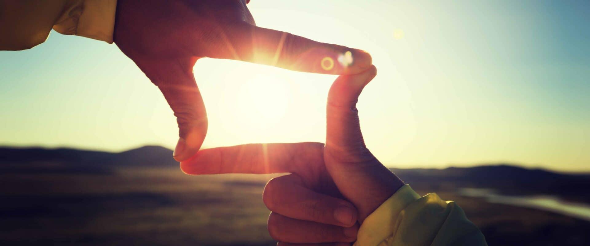 Erneuerbare Energie - Solarenergie: Sonne mit Händen eingefangen